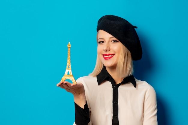 Piękna francuska kobieta w berecie trzyma miniaturową wieżę eifla Premium Zdjęcia