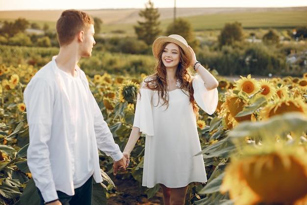 Piękna i stylowa para w polu z słonecznikami Darmowe Zdjęcia