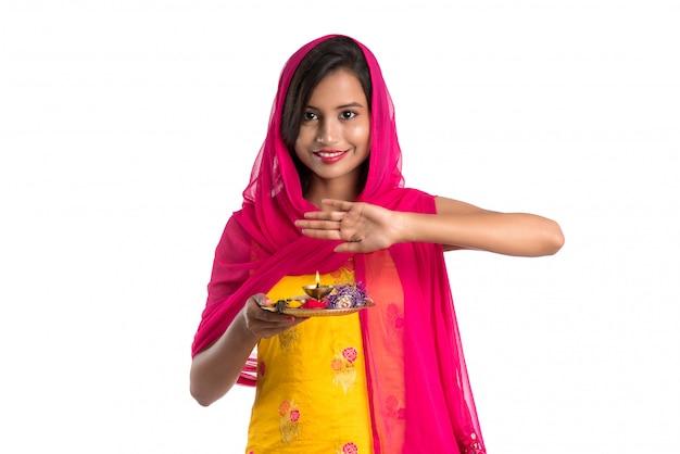 Piękna indyjska młoda dziewczyna trzyma pooja thali lub wykonuje cześć Premium Zdjęcia
