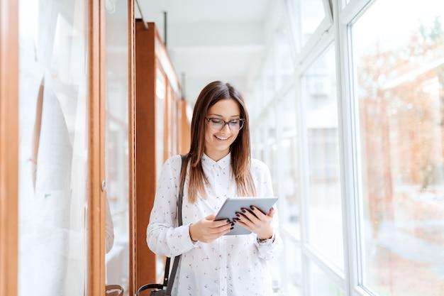 Piękna Kaukaska Brunetki Pozycja Obok Noticeboard I Używać Pastylkę Podczas Gdy Stojący W Uniwersyteckim Budynku. Premium Zdjęcia