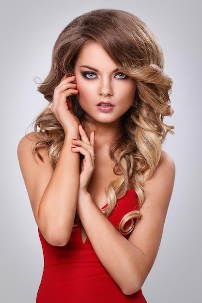 Piękna kędzierzawa kobieta w czerwieni sukni Darmowe Zdjęcia