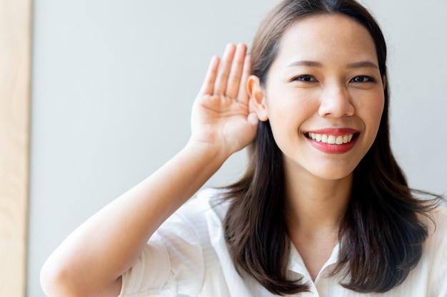 Piękna Kobieta Azji Lekarz Uśmiecha Się I Użyj Dłoni Za Uchem, Aby Spróbować Posłuchać Koncepcji Głuchoty Premium Zdjęcia