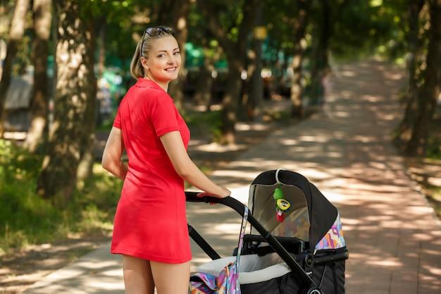 Piękna Kobieta Chodzi Dziecka W Parku Premium Zdjęcia
