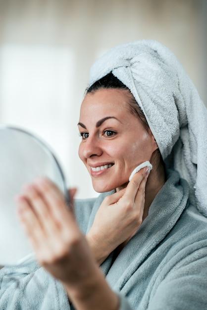 Piękna kobieta czyści jej twarz z bawełnianym ochraniaczem, trzyma lustro. Premium Zdjęcia
