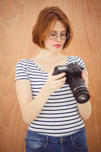 Piękna kobieta hipster, patrząc na ekran aparatu cyfrowego Premium Zdjęcia