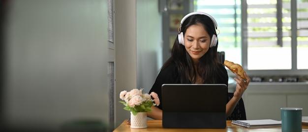 Piękna Kobieta Je Rogalika, Korzystając Z Tabletu Przy Drewnianym Biurku. Premium Zdjęcia