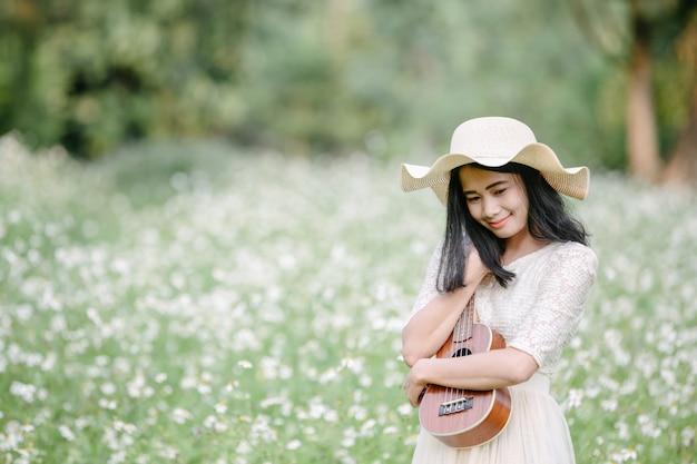 Piękna kobieta jest ubranym śliczną białą suknię i trzyma ukulele Darmowe Zdjęcia