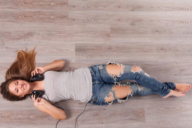 Piękna kobieta kłama na podłoga z hełmofonami Darmowe Zdjęcia