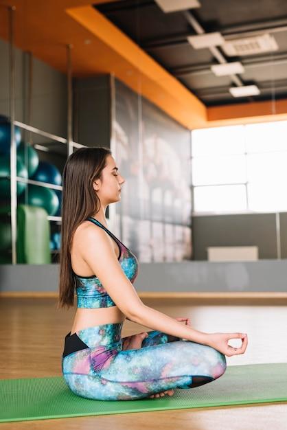 Piękna kobieta medytuje siedzieć na joga macie Darmowe Zdjęcia