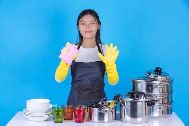 Piękna kobieta myje naczynia przed nim na niebiesko. Darmowe Zdjęcia