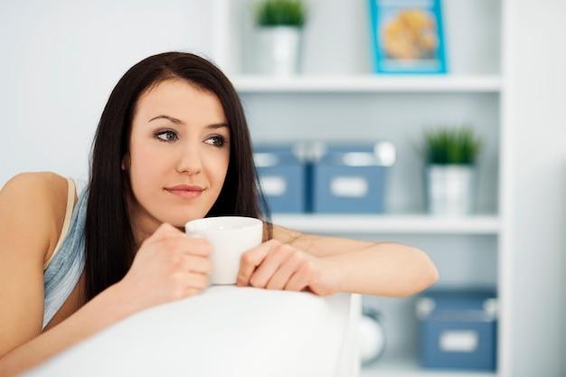 Piękna Kobieta Na Kanapie Z Filiżanką Kawy Darmowe Zdjęcia