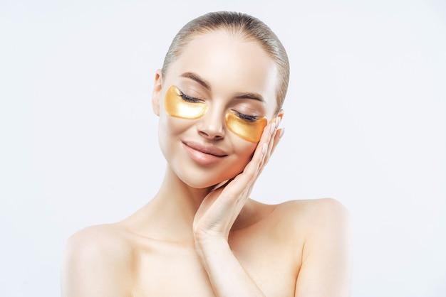 Piękna Kobieta O Ciemnych Włosach, Zamyka Oczy I Dotyka Twarzy, Nakłada Złote Plamy Kolagenowe Premium Zdjęcia