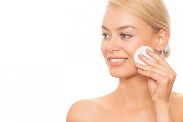 Piękna kobieta oczyszcza jej skórę Premium Zdjęcia
