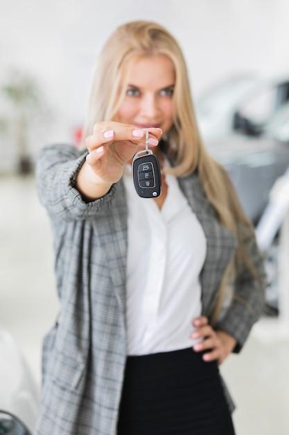 Piękna kobieta pokazuje przy kluczami samochodowy środka strzał Darmowe Zdjęcia
