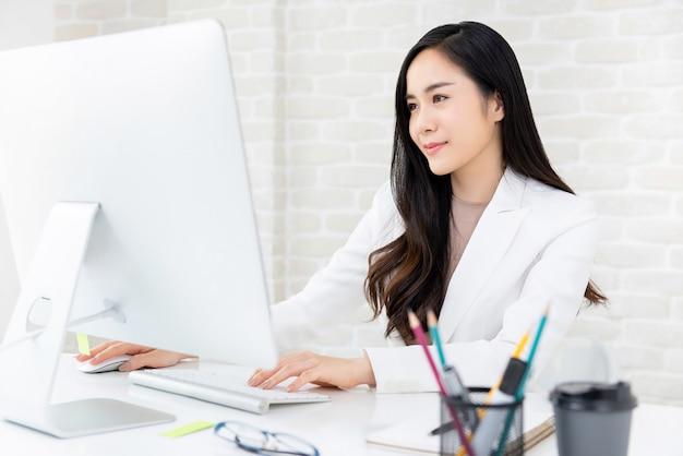 Piękna kobieta pracująca używa komputer w biurze Premium Zdjęcia