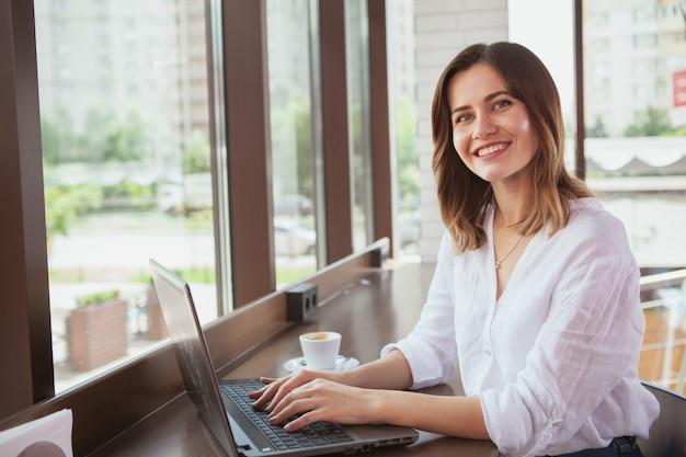 Piękna kobieta przy sklep z kawą Premium Zdjęcia