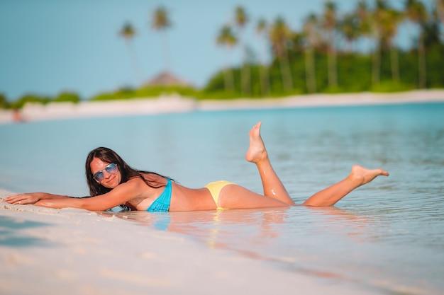 Piękna Kobieta Relaksuje Przy Białego Piaska Tropikalną Plażą Premium Zdjęcia