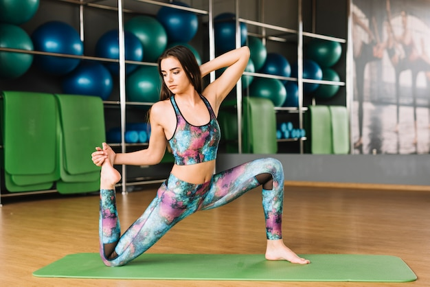 Piękna kobieta, rozciąganie mięśni ciała na zielony matę do jogi Darmowe Zdjęcia