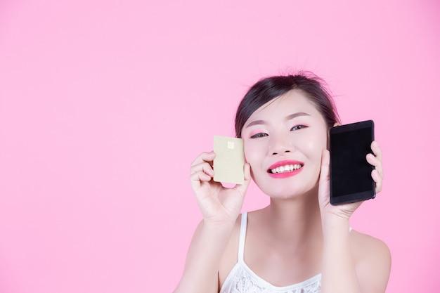 Piękna Kobieta Trzyma Kartę Na Różowym Tle I Smartphone Darmowe Zdjęcia