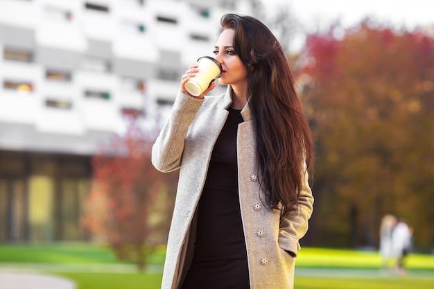 Piękna kobieta trzyma papierową filiżankę i cieszy się spacer w mieście Premium Zdjęcia