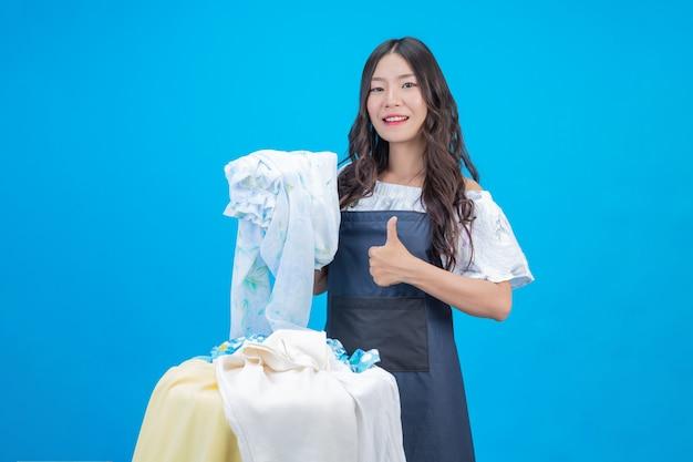 Piękna kobieta trzyma szmatkę przygotowaną do prania na niebiesko Darmowe Zdjęcia