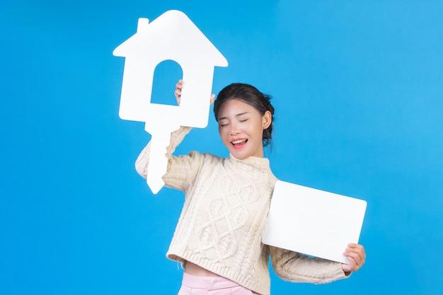 Piękna kobieta ubrana w nową koszulę, biały dywan z długimi rękawami z symbolem domu i białym napisem na niebieskim. trading. Darmowe Zdjęcia