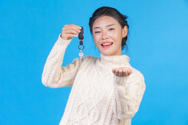 Piękna kobieta ubrana w nowy biały dywan z długimi rękawami, trzymająca w ręku brelok na niebiesko. trading s. Darmowe Zdjęcia