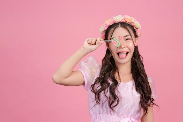 Piękna Kobieta Ubrana W Różową Księżniczkę Bawi Się Swoim Słodkim Cukierek Na Różu. Darmowe Zdjęcia