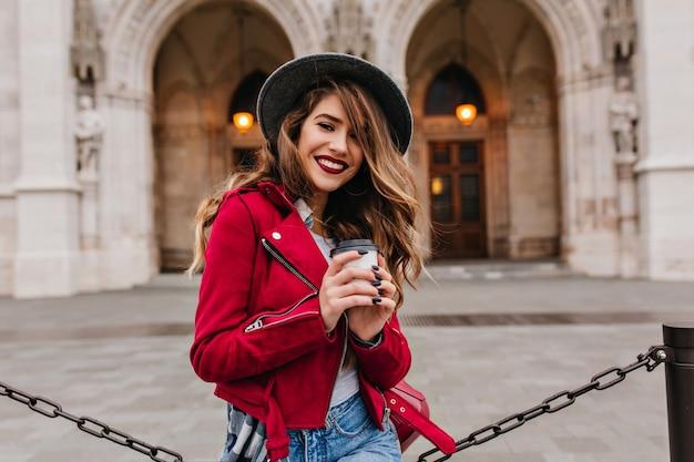Piękna Kobieta Uśmiecha Się Do Kamery Pijąc Latte Obok Muzeum Darmowe Zdjęcia