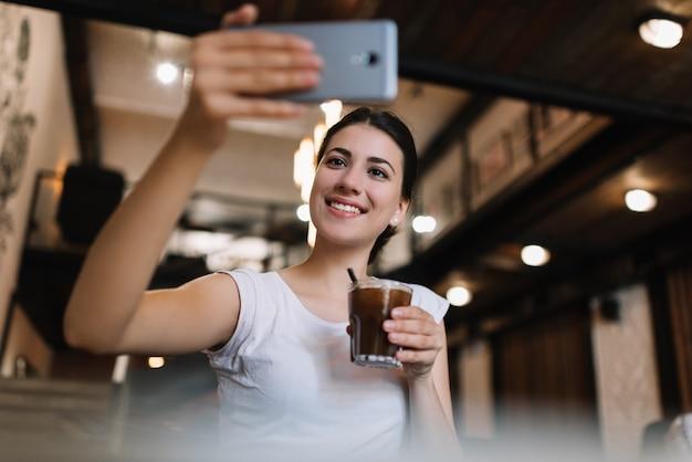 Piękna Kobieta Używa Smartphone, Bierze Selfie, Pije Koktajl W Kawiarni. Uśmiechnięty Bloger Streaming Wideo Online Premium Zdjęcia