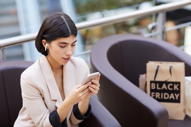 Piękna Kobieta Używa Smartphone Podczas Gdy Relaksujący W Zakupy Centrum Handlowym Premium Zdjęcia