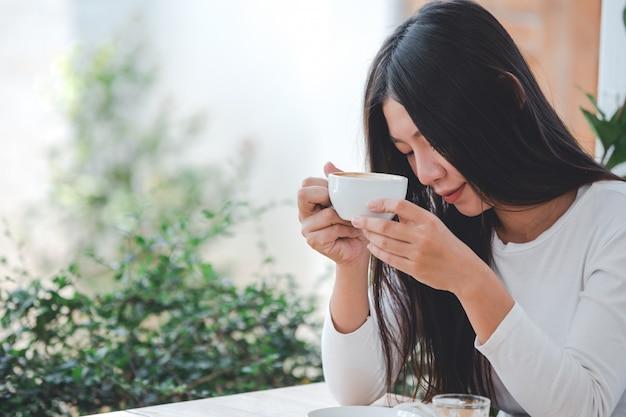Piękna Kobieta W Białej Koszuli Z Długimi Rękawami, Siedząca W Kawiarni Darmowe Zdjęcia