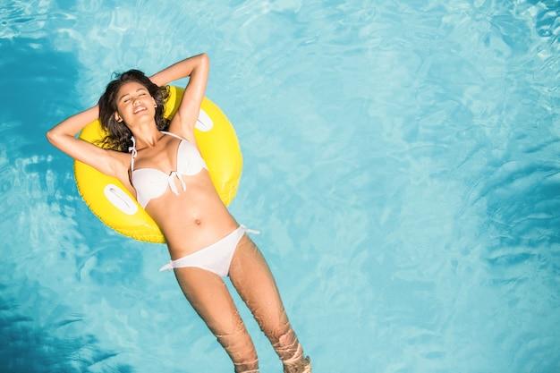 Piękna kobieta w białym bikini unosi się na nadmuchiwanej tubie w pływackim basenie Premium Zdjęcia