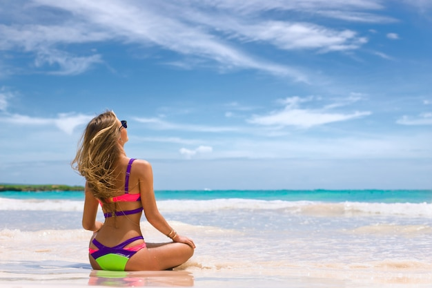 Piękna Kobieta W Bikini Na Tropikalnej Plaży. Dziewczyna Siedzi Na Piasku Plecami Do Kamery I Patrzy Na Ocean. Premium Zdjęcia