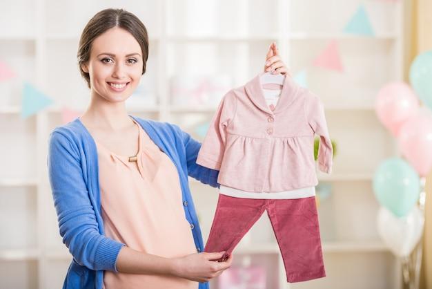 Piękna kobieta w ciąży trzyma ubrania dla dzieci. Premium Zdjęcia