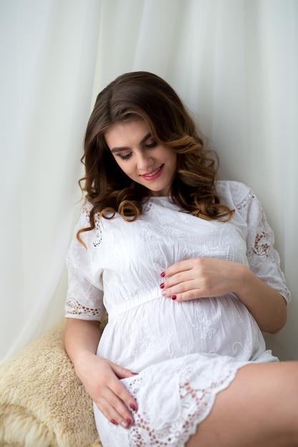 Piękna Kobieta W Ciąży Z Doskonałym Makijażem I Fryzurą, Ubrana W Białą Sukienkę, Siedząca Na Kanapie Premium Zdjęcia