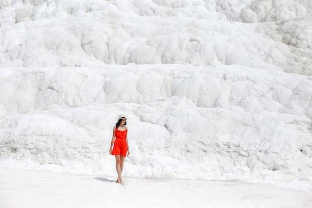 Piękna Kobieta W Czerwonej Sukience Stoi Na Tle Białych Gór Premium Zdjęcia