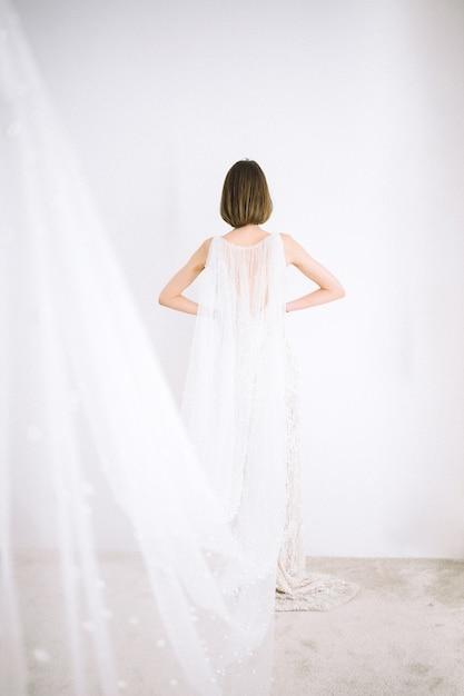 Piękna Kobieta W Długiej Białej Sukni Stojącej W Pokoju Z Białymi ścianami Darmowe Zdjęcia