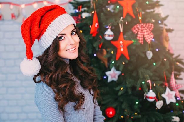 Piękna Kobieta W Kapeluszu Santa Na Choince. świętujemy Nowy Rok I Boże Narodzenie. Premium Zdjęcia