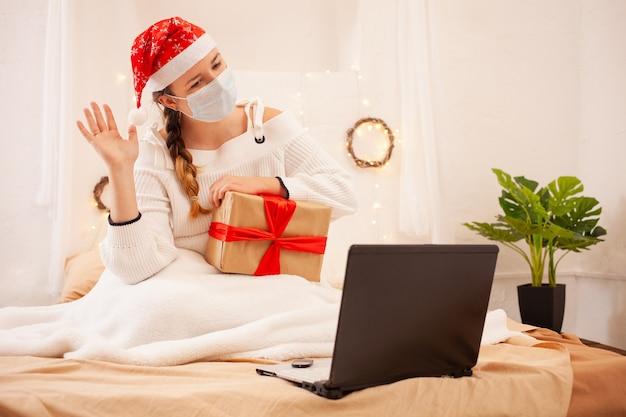 Piękna Kobieta W Masce I świątecznej Czapce Gratuluje Swoim Przyjaciołom Przez Rozmowę Wideo Premium Zdjęcia