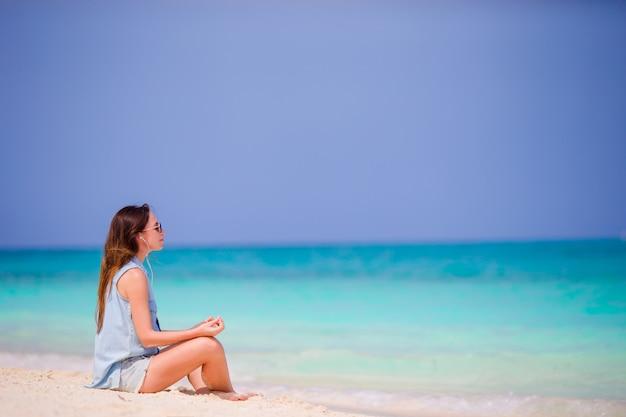 Piękna Kobieta W Medytacji Na Plaży. Szczęśliwa Dziewczyna Relaksuje Na Tropikalnej Plaży W Joga Pozyci Premium Zdjęcia