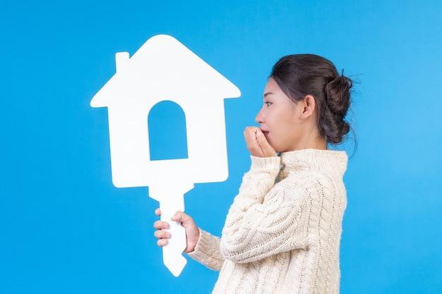 Piękna kobieta w nowej białej koszuli z długimi rękawami z symbolem domu. handel domami. Darmowe Zdjęcia