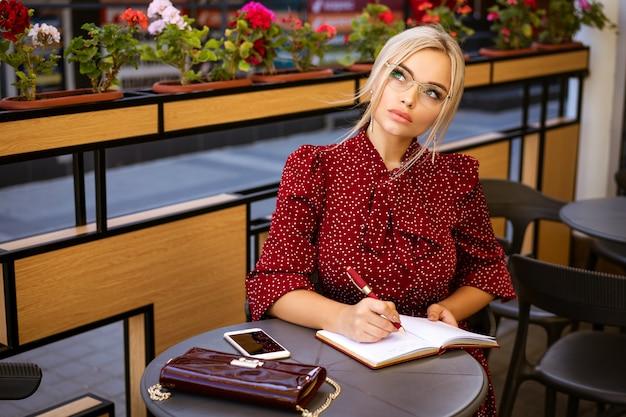 Piękna Kobieta W Okularach W Czerwonej Sukience Siedzi Z Notatnikiem W Kawiarni Premium Zdjęcia