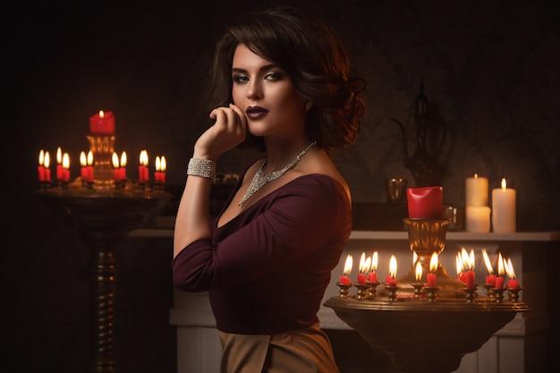 Piękna Kobieta W Pokoju Z Dużą Ilością świec Premium Zdjęcia