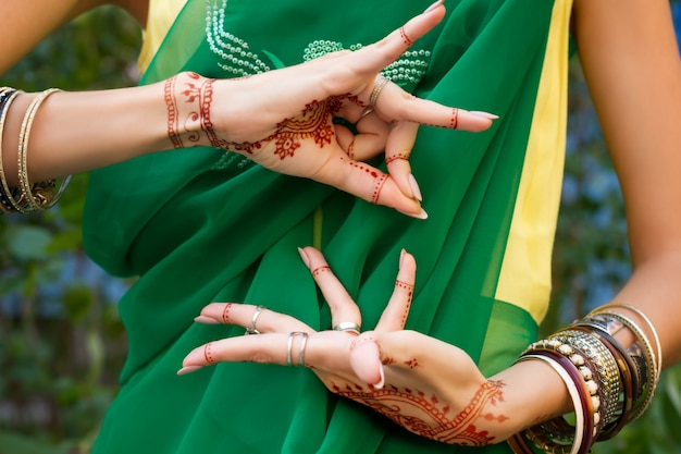 Piękna Kobieta W Tradycyjnej Muzułmańskiej Indyjskiej ślubnej Zielonej Sukience Sari Z Henną Biżuterią Z Tatuażem I Bransoletkami Robi Ręce Nritta Odissi Samyuta Hastas Dance Movement Alapadma Bramara Concept Background Premium Zdjęcia