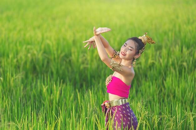 Piękna Kobieta W Tradycyjnym Tajskim Stroju, Uśmiechając Się I Stojąc W świątyni Darmowe Zdjęcia