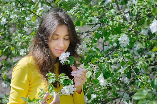 Piękna Kobieta Wącha Kwiatu W Wiosna Ogródzie Premium Zdjęcia