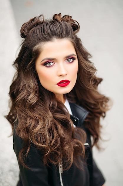 Piękna kobieta z długimi kręconymi włosami w skórzanej kurtce. Premium Zdjęcia