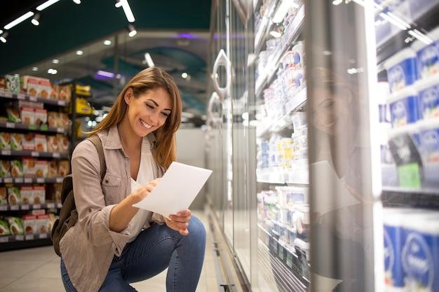 Piękna Kobieta Z Listy Zakupów Kupuje Jedzenie W Supermarkecie Darmowe Zdjęcia