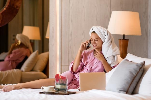 Piękna kobieta z ręcznikiem na głowie opowiada na telefonie w sypialni w domu. poranna rutyna. Premium Zdjęcia